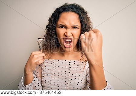 Young beautiful woman with curly hair holding eyelases curler over white background annoyed and frustrated shouting with anger, crazy and yelling with raised hand, anger concept