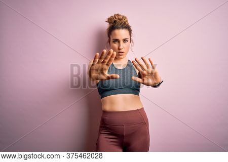 Young beautiful blonde sportswoman doing sport wearing sportswear over pink background Moving away hands palms showing refusal and denial with afraid and disgusting expression. Stop and forbidden.