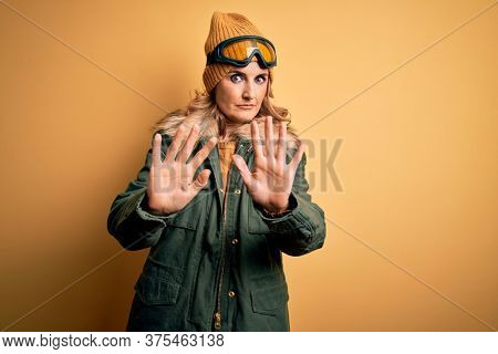 Middle age beautiful blonde skier woman wearing snow sportwear and ski goggles Moving away hands palms showing refusal and denial with afraid and disgusting expression. Stop and forbidden.