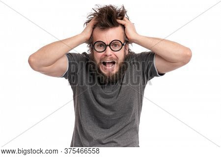 Crazy Scared or Shocked Bearded Man with funny Haircut in Eyeglasses looks Worried. Screaming Silly, Afraid or Surprised guy holding his Head, isolated on white background.