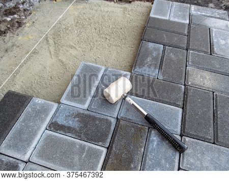 A White Rubber Mallet Lies On The Surface Of A Gray Brick Paving Slab. Tools And Materials For Pavin