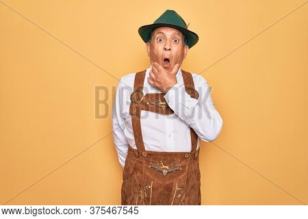 Senior grey-haired man wearing german traditional octoberfest suit over yellow background Looking fascinated with disbelief, surprise and amazed expression with hands on chin