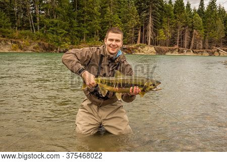 Kitimat, British Columbia, Canada - July 27th, 2015: A Happy Sport Fisherman Proudly Holding Up His