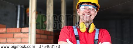 Happy Builder Stands Near Brickwork And Smiles. Efficiency Construction Personnel, Mood And Comfort