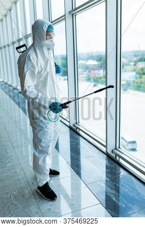 Coronavirus Pandemic. A Disinfector In A Protective Suit And Mask Sprays Disinfectants In Office. Pr
