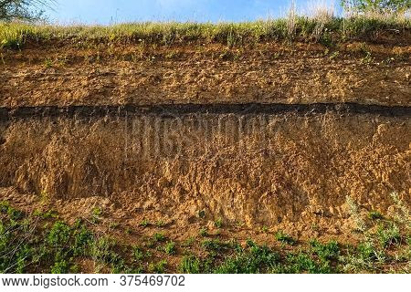 Soil Slice In A Quarry. Visible Soil Layers. Traces Of Sedimentation. The Slopes Are A Quarry With A