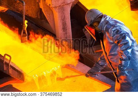 Worker At A Steel Mill. The Worker Mixes The Molten Metal.