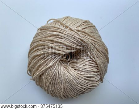A Skein Of Beige Yarn On A White Background. Photo From Above. Knitting, Needlework, Hobbies.