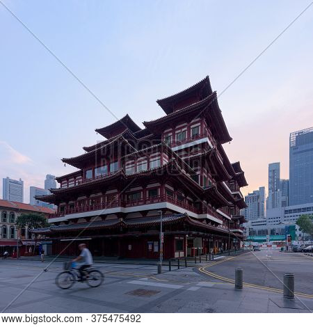 Singapore - 31 Oct 2019: A Man Rides A Bicycle In Front Of The Buddha Tooth Relic Chinese Temple, At
