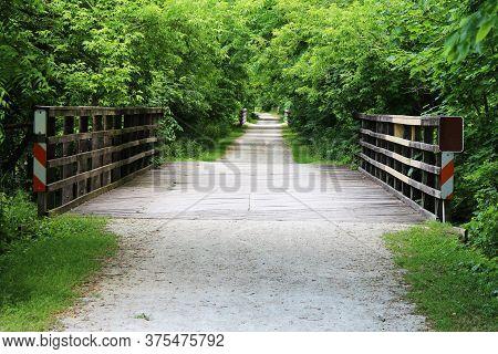 A Dirt Path Over Several Bridges Through The Lush Rural Countryside