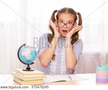 Education And School Concept. Smiling Happy Child In Glasses Is Sitting At The Desk. Cute Little Stu