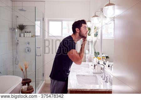 Man Wearing Pyjamas Standing At Sink Putting On Moisturizer In Bathroom
