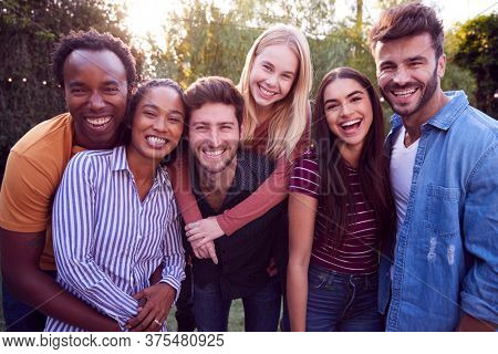 Portrait Of Group Of Multi-Cultural Friends Enjoying Outdoor Summer Garden Party