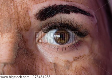 Beauty Day. Close-up Of A Woman`s Face. The Woman Has A Clay Face Mask And Eyebrows Painted Black.th