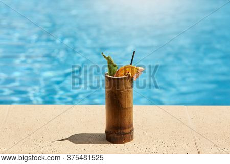 Exotic Cocktail In Wooden Glass With Lemon And Drinking Tube Standing On Poolside With Blue Pool's W