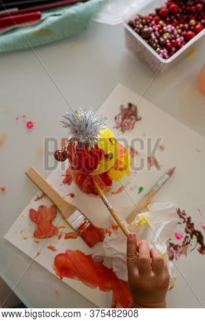Top View Of A Child Creating And Painting With Various Materials.