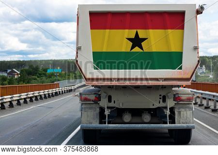 Big  Truck With The National Flag Of  Ghana Moving On The Highway, Against The Background Of The Vil