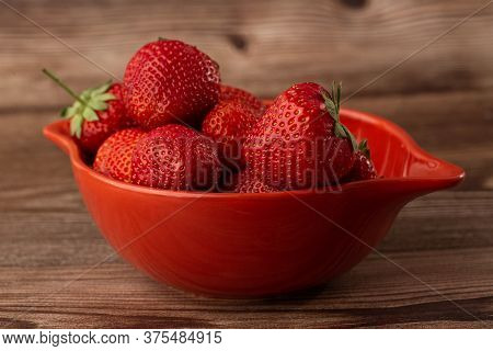 Fresh Strawberries In A Bowl On Wooden Table. Fresh Nice Strawberries. Strawberry Field On Fruit Far