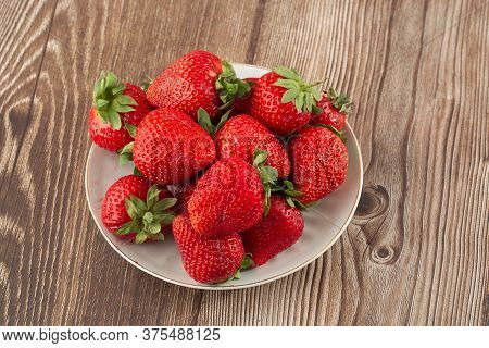 Fresh Strawberries In A Plate On Wooden Table. Fresh Nice Strawberries. Strawberry Field On Fruit Fa
