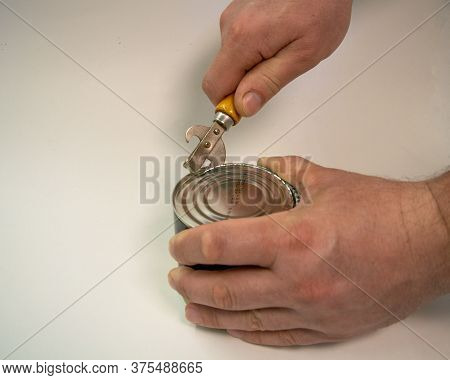 A Man Opens An Tin Can. He's Got An Opener With A Wooden Handle In His Hand. Close Up.