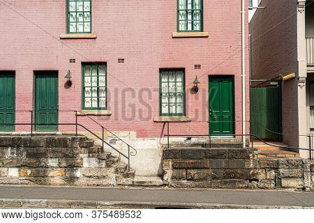 Exterior Of Old Red Brick Townhouse With Green Doors