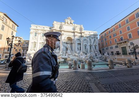 Rome, Italy - 10 March 2020: A City Police Man Wearing A Face Mask Walks Across The Deserted Trevi F