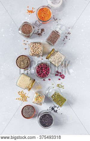 Legumes, Seeds And Cereals On A Gray Background. Healthy Food. Top View, Copy Of Space.