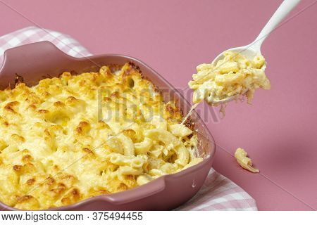 Grabbing A Spoon Of Cheesy Macaroni From The Tray With Mac And Cheese Freshly Baked. Mac And Cheese