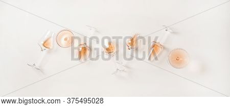 Flat-lay Of Rose Wine In Glasses Over Plain White Background
