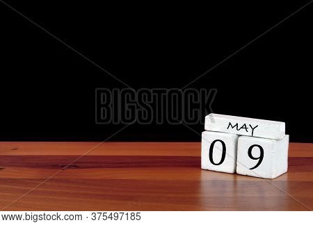 9 May Calendar Month. 9 Days Of The Month. Reflected Calendar On Wooden Floor With Black Background
