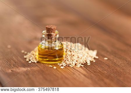 Sesame Oil With Sesame Seeds On The Wooden Table.