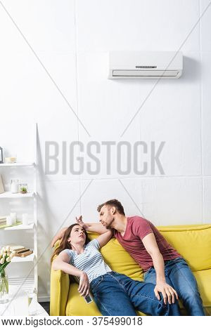 Young Couple Suffering From Heat While Sitting Home With Broken Air Conditioner