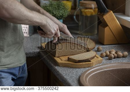 Mans Hand Cutting Rye Bread On Wooden Board With Knife On Rustic Style Kitchen. Set Of Knives And So
