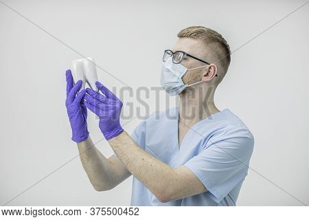 Young Handsome Dentist Doctor Wearing Glasses And Protective Mask Holds Model Of Molar Tooth In Hand