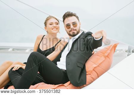 Young Loving Couple Sitting On Deck Of Sailboat During Sea Trip, Looking Far Away And Pointing To Ho