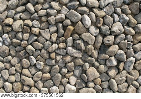 Grey Dark Colorful Pebbles Background. Top View. Backdrop Made Of Many Small Round Smooth Sea Stones