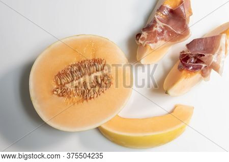 Half Melon Next To Some Slices With Thin Cured Ham Slices On Top Of Them.tasty Food And Lifestyle Co
