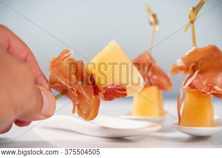 A Male Hand Holding A Skewer Made Of A Small Melon Piece And A Thin Slice Of Cured Ham,
