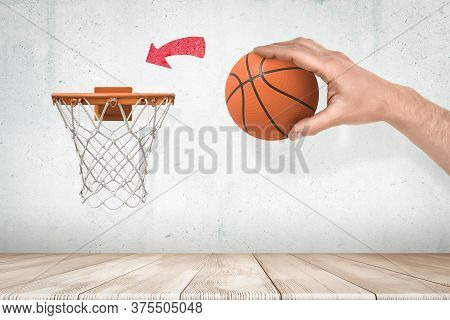 Mans Hand Holding Orange Basketball Ready To Throw It Into Basketball Hoop Fixed On Grungy White Wal