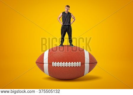 Tiny Athletic Man In Black Tracksuit Standing On Brown Oval Ball For American Football On Amber Back
