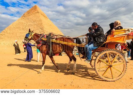 Cairo, Egypt - December 8, 2018: Tourists Riding A Horse Chariot Near Pyramids Of Giza In Cairo, Egy