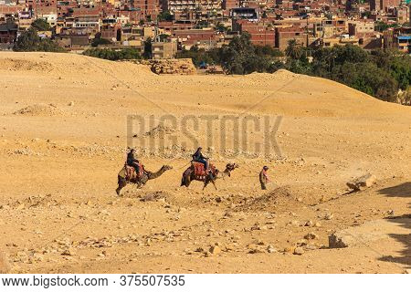 Cairo, Egypt - December 8, 2018: Tourists Riding Camels On Giza Plateau Against Cityscape Of Cairo