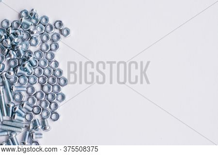 Chrome-plated Screw Nuts And Bolts Top View. Bolts And Nuts On A White Background. Construction Indu