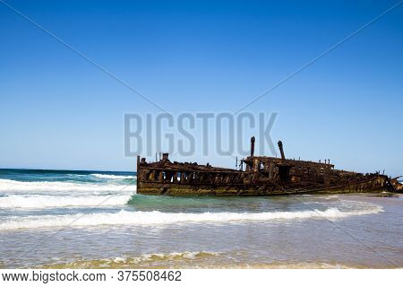 Photograph Of The Shipwreck Of The Ss Maheno On Fraser Island With A Cloudless Sky In The Background