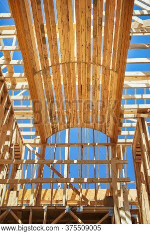 New Construction Home Framing Against Blue Sky. Ceiling Frame And Arch Structure Details Above Hallw