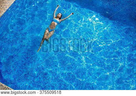 Top View Of Girl Swimming In Pool. Beautiful Girl With Perfect Slim Body In Blue Bikini In Pool. Res