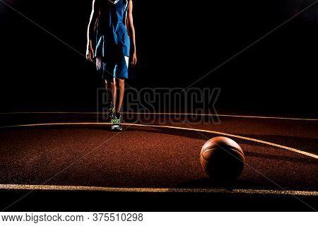 Basketball. A Teenage Boy In A Blue Sports Uniform Walks Confidently Towards A Basketball Ball Lying