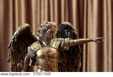 Statuette Of The Archangel Michael On A Velour Background.