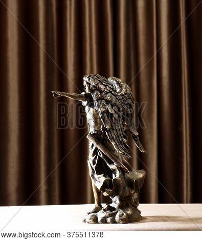 A Bronze Statuette Of The Archangel Michael Points A Finger Forward.