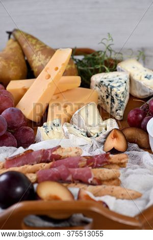Antipasto. Dish With Crispy Grissini Wrapped In Sun-dried Bacon, Slices Of Brie Cheese, Camembert, B